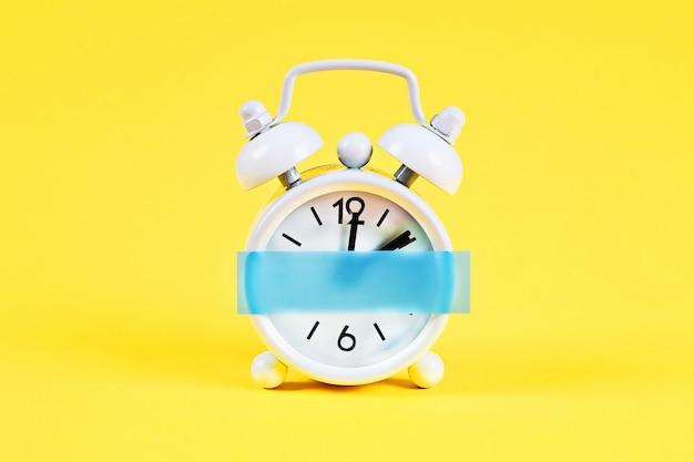 白い目覚まし時計黄色のパステル背景。クロックに空白の付箋。スペースコピー。最小限のコンセプト。