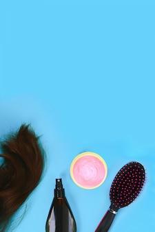 髪、髪のマスク、櫛、パステルブルーの背景にスプレー。ヘアケアの概念。コピースペース、トップビュー。
