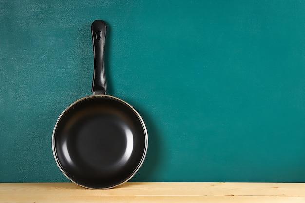 青緑色の背景に木製の棚に黒のフライパン。キッチン用品。