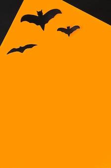 ハロウィーンのコンセプト。オレンジ色の背景のコウモリ。