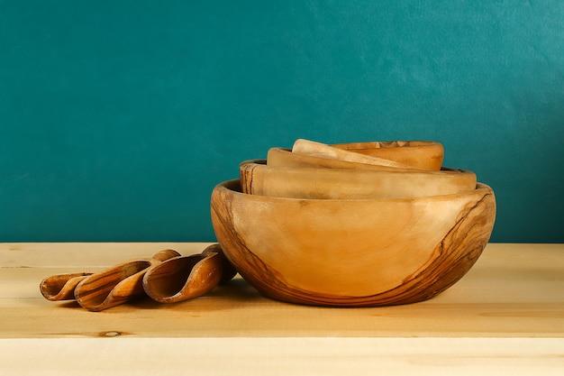 木製の道具。木製プレート、カップ、ボウル。棚の上の料理。キッチン用品。