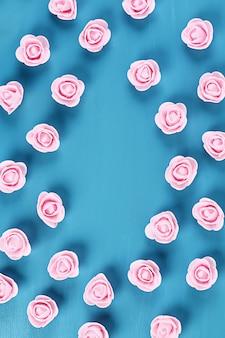 青色の背景に小さなバラ。上面図。夏の背景。平干し。