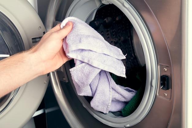 Человек, принимая цвет одежды из стиральной машины. барабан стиральной машины полон грязного белья в ванной комнате.