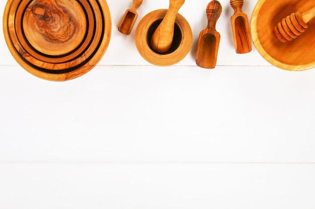 ノートブックと木製の調理器具で、コピースペースのある白い木製の背景に。