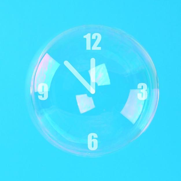 青いパステル調の背景に時計の形の矢印の付いたシャボン玉。ミニマリズム
