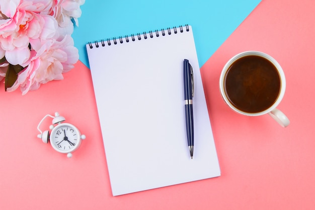 ピンクのパステル調の背景に青いペンを持つ空のノートブック。モックアップ、フレーム、テンプレート