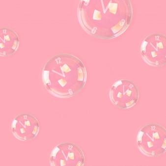 ピンクのパステル調の背景に時計の形の矢印の付いたシャボン玉。ミニマリズム