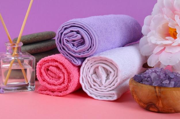 ピンクのパステル調の背景にスパ。タオル、石、アロママス、紫の塩浴、ピンクの花