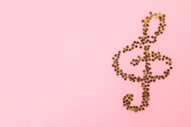 ピンクのパステル調の背景に横たわっている星空の黄金の紙吹雪の音符。