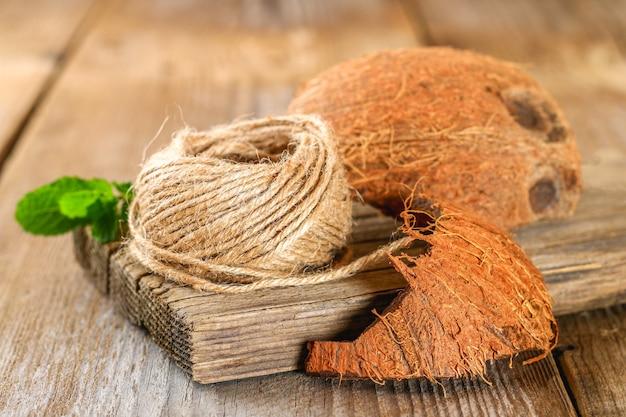 古い木製のテーブルの上の繊維のコイアとココナッツの殻のロープ。