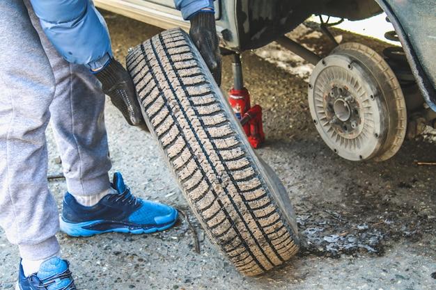 車両のタイヤを交換しながらラグナットを手動で交換する。