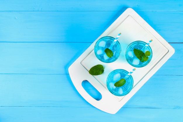 青い氷と青いテーブルの上の白い木の板にグラスのミントカクテル。上面図。