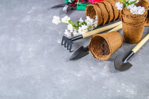 園芸工具、灰色のコンクリート背景上の鉢。スペースをコピーしてください。