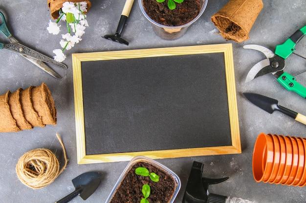 園芸工具および灰色のコンクリート背景の上の鉢。黒板。上面図、スペースをコピーします。