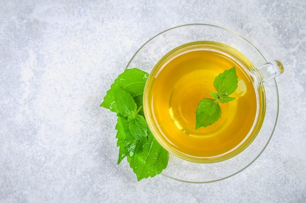 灰色のコンクリートテーブルの上の新鮮な緑のイラクサとハーブのイラクサ茶の透明なガラスのコップの葉。