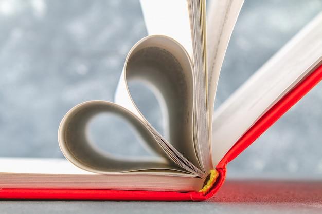 赤い表紙の本のページはハートの形で作られています。バレンタインデーのコンセプトです。