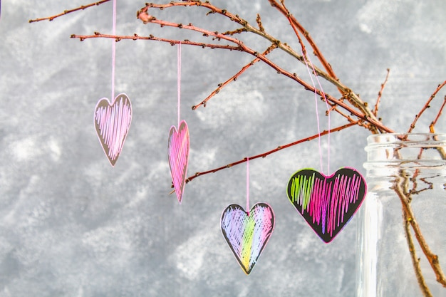 黒ピンクの心は灰色のコンクリート背景の枝にハングします。バレンタインデーのコンセプトです。
