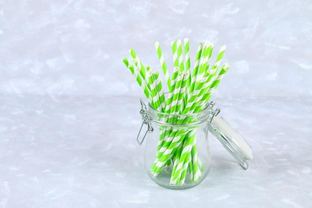 灰色の背景上の瓶に緑色のストライプ紙使い捨てチューブ