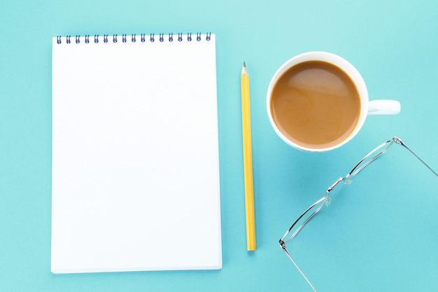 空白のページと青い背景上のコーヒーとノートブックを開くの上から見た画像