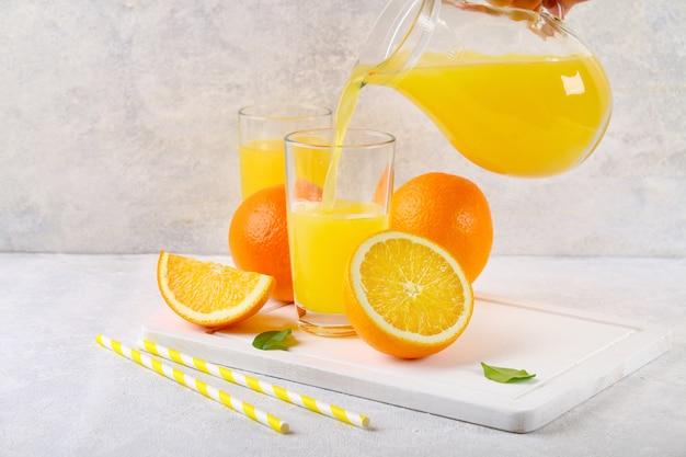 ガラスのコップとオレンジと黄色のチューブのスライスと新鮮なオレンジジュースの投手