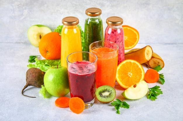 Зеленые, желтые, фиолетовые смузи в смородиновых бутылках, петрушка, яблоко, киви, апельсин на сером столе.