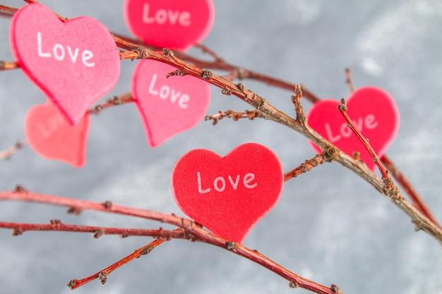 赤いハートの愛は、コンクリートの背景に枝にハングアップします。木が大好きです。