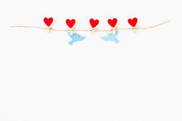バレンタインデーのレイアウト。赤いハートと鳩の木製の洗濯はさみを愛する白い背景の麻ひも