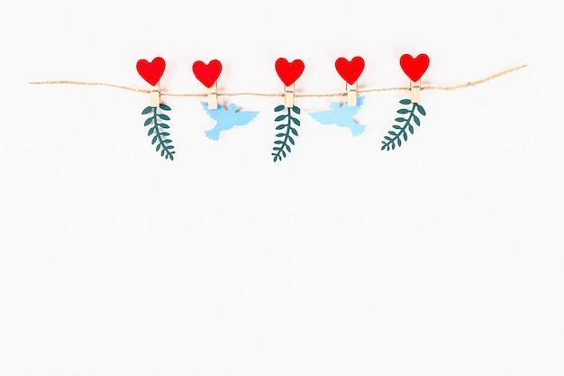 バレンタインデーのレイアウト。赤いハートと鳩が麻ひものひもに木製の洗濯はさみに大好き