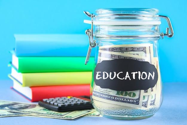 Банк с долларами и калькулятором, книгами на серой предпосылке. финансы, копилка, образование.