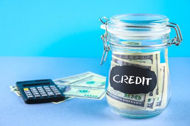 Банк с долларами и калькулятором на серой предпосылке. финансы, копилка, консервация, кредит.