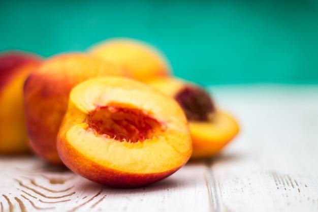 Много свежих персиков на белом столе