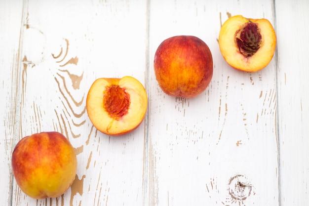Много свежих персиков на белом столе. вид сверху.