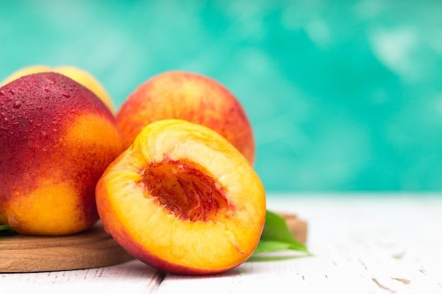 白いテーブルに新鮮な桃の多く