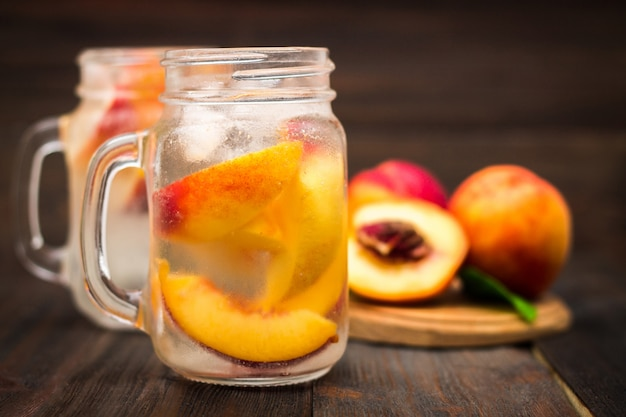 自家製桃のメイソンジャーガラスは素朴な木製の背景に水をアイス。