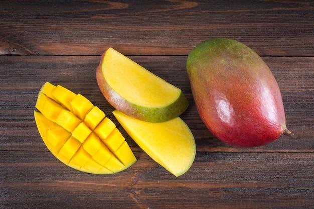 木製の背景にトロピカルフルーツマンゴー、全体またはスライス。