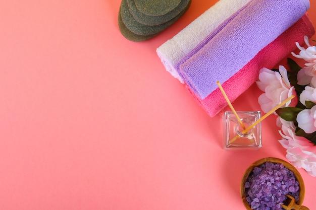 ピンクのパステルの背景にスパ。タオル、石、アロママッサー、パープルソルトバス、ピンクの花。