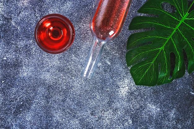 ワイングラス、ボトル、トロピカルリーフのワイン。上面図。灰色のバックグラウンドでワインドリンク