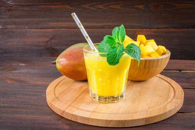 Смузи манго с соломой и мятой в стеклянном стакане. тарелка с нарезанным манго.