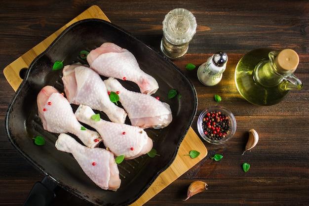Сырые куриные ножки в сковороде на деревянном столе. мясные ингредиенты для приготовления пищи. вид сверху.