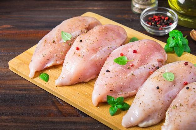 木製のテーブルの背景にまな板の上の生の鶏肉の切り身。