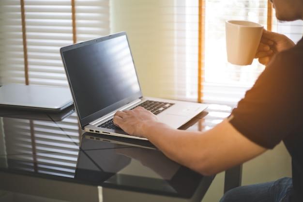 ビジネスマンのラップトップに取り組んで、若い男が技術を使用しています