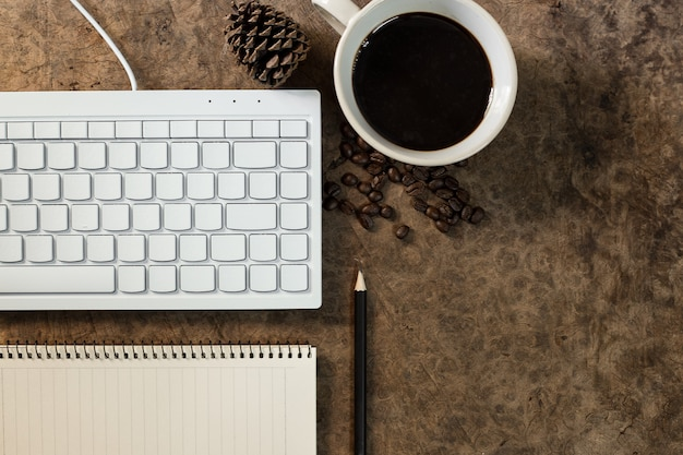 Работайте с клавиатурой и держите кофейную кружку на деревянном полу.