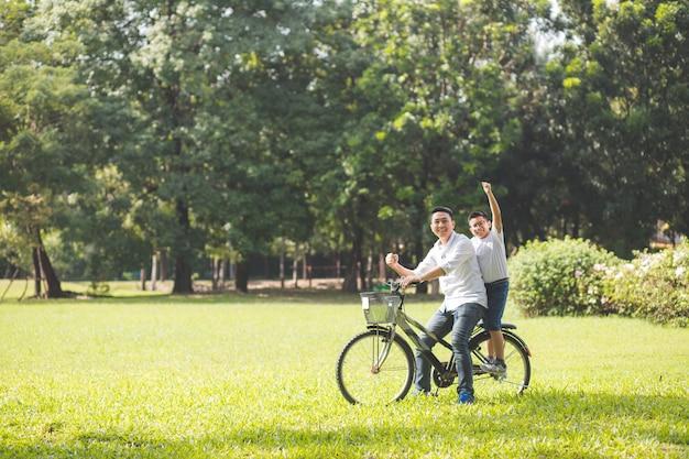 Азиатский отец и дети. тайцы. они едут по траве в парке. они оба припарковывают свои велосипеды и поднимают кулаки с улыбающимся и счастливым лицом.