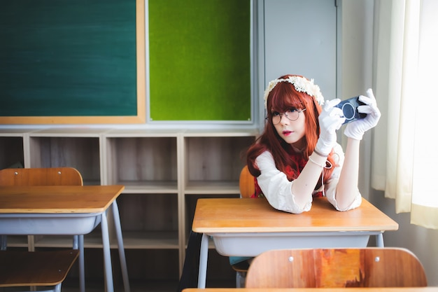 Красивая азиатская женщина, тайская женщина сидит в портативной игровой консоли в классе.