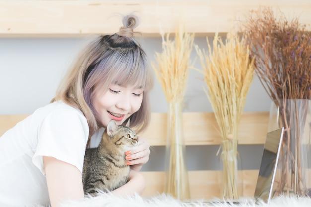 Короткие волосы женщины, красивые и милые женщины. азиатские люди носят белые футболки. она спит с кошкой в гостиной с улыбающимся и счастливым лицом.