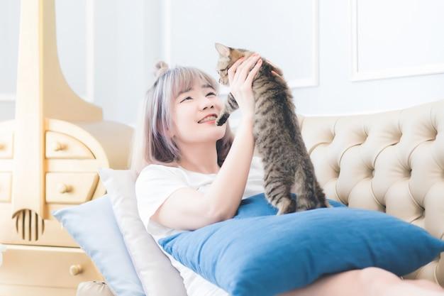 Красивая азиатка, тайка, лежит с кошкой на диване с улыбающимся и счастливым лицом в гостиной