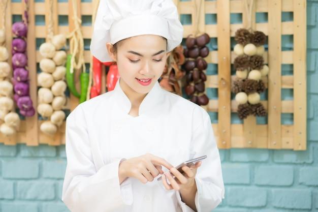 アジアの女性シェフは、タイのレストランのキッチンにあるモバイルアプリケーションを介して、顧客が注文した食べ物を受け取ります。
