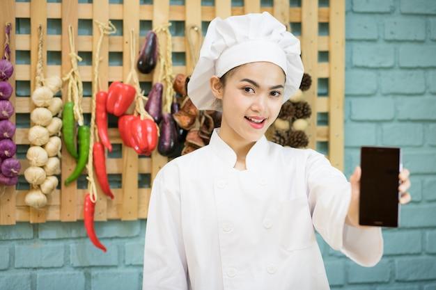 シェフは白い調理服を着て、持ち上げて、台所にさまざまなスパイスをかけた携帯電話を持ちました。スマホのアプリで料理をオンラインで注文するというコンセプトで