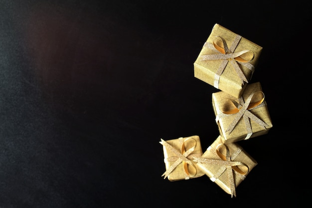 Некоторые золотые подарочные коробки на черном фоне, сосредоточиться на верхней коробке.