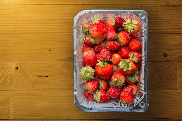 木製のプラスチック箱に赤いイチゴ